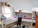 """Moshe poses in his sister's bedroom. HIs father called the design, """"peculiar"""" and his mother thinks """"he [the architect] went bankrupt."""""""