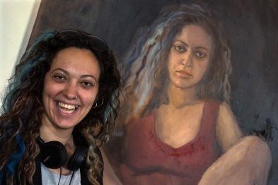 A Beita artist poses alongside her portrait by Zoe Bray